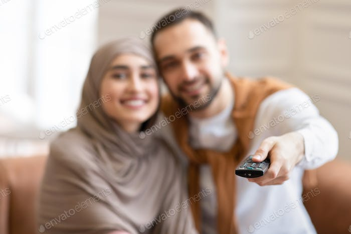 Cheerful Muslim Couple Watching TV Sitting On Sofa At Home