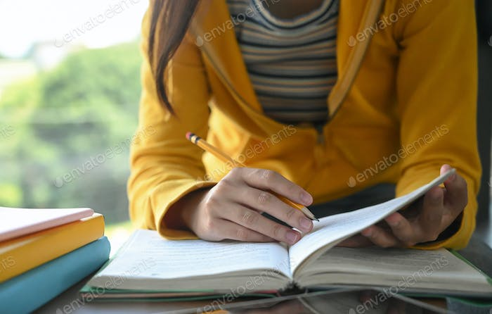 Students are reading books and taking notes for exam preparation.