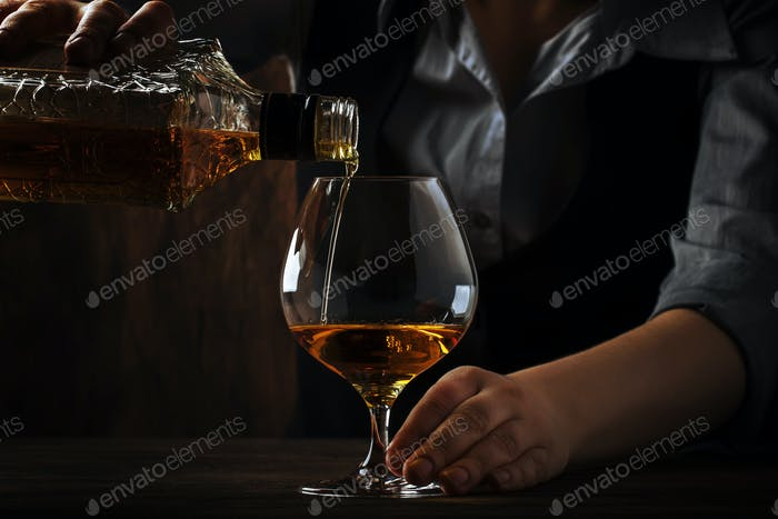 The bartender pours the cognac