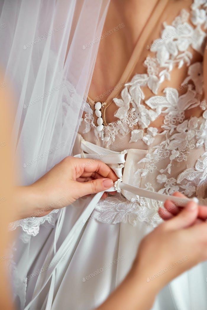 Die Braut zieht sich im Zimmer an.