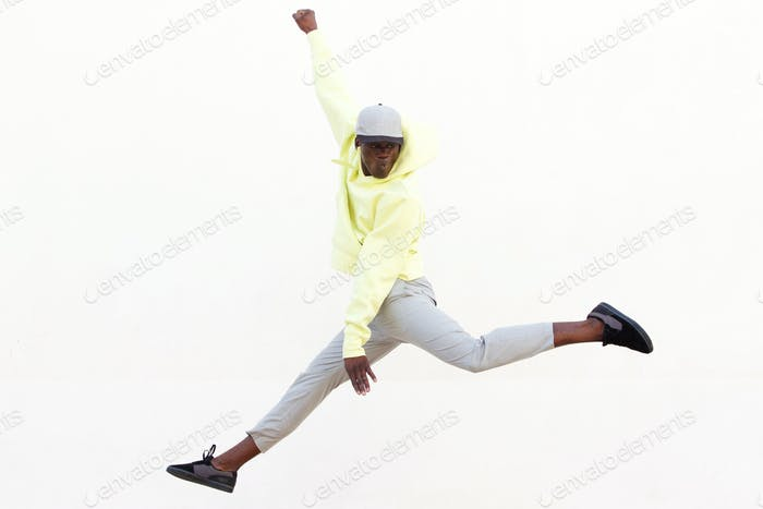 stylish young African American man jumping and dancing on white background