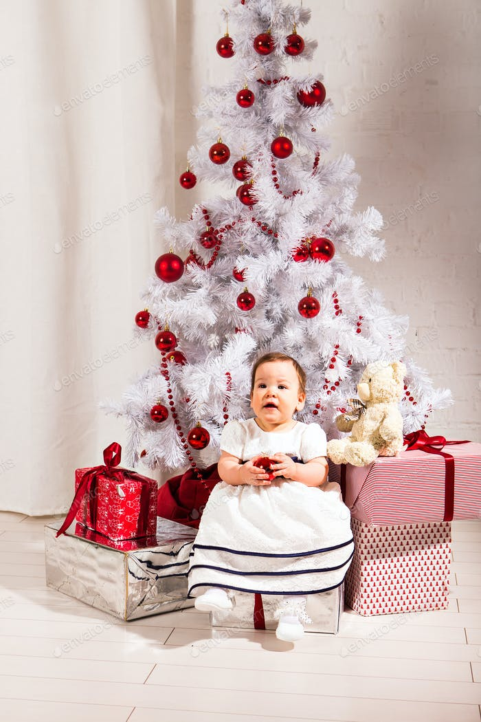 Baby  girl sitting under decorated christmas tree. New year and Christmas concept