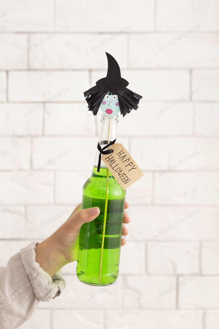 Green party drink with paper witches head over bricks wall