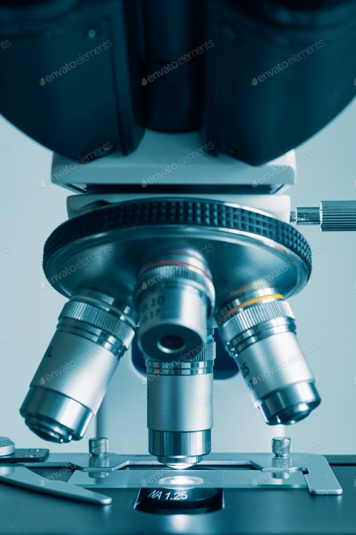 Modern microscope with metal lens at laboratory.