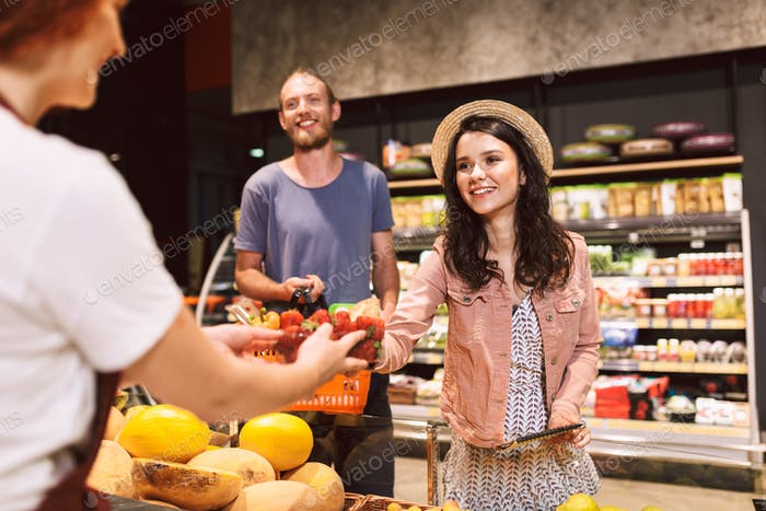 Young beautiful couple with basket full of products happily buyi