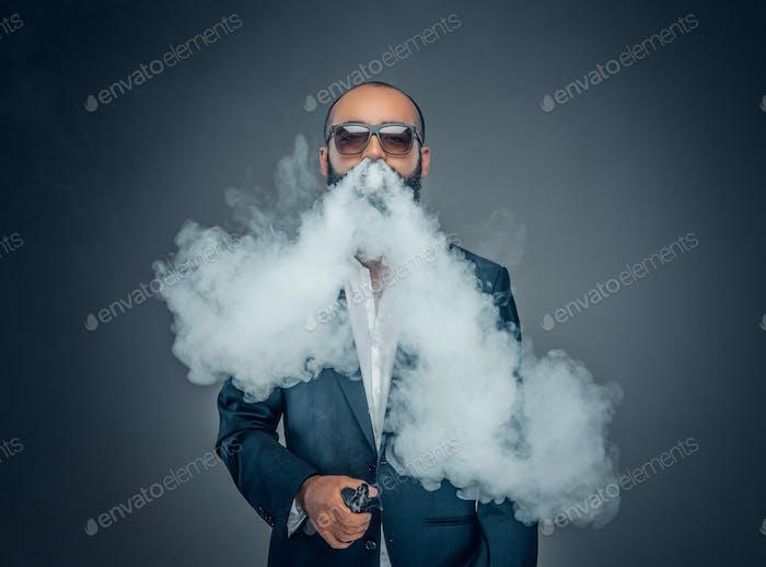 Beard male smoking electronic pipe.