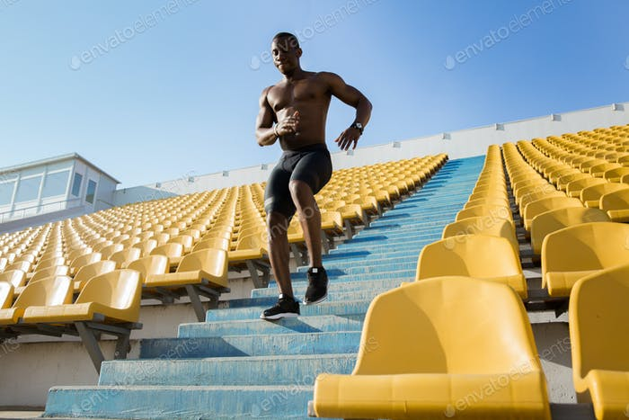 Sporty young african man runner running upstairs