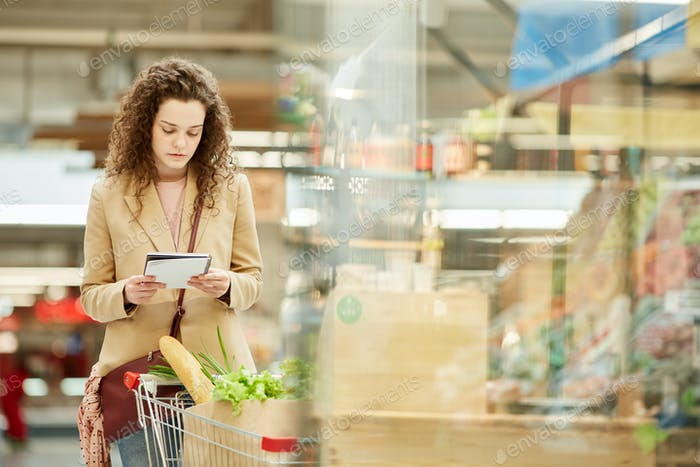 Young Woman Buying Food in Grocery Store