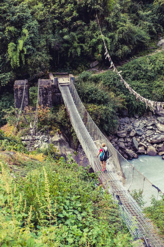 Woman backpacker crossing suspension bridge in Himalayas Nepal