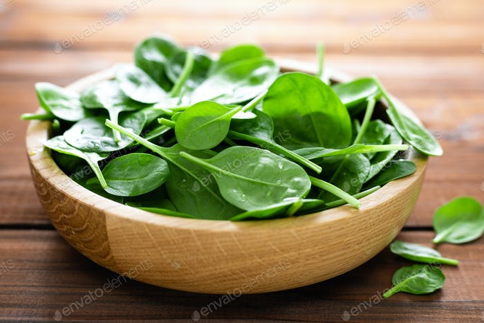 Fresh spinach leaves on wooden background. Healthy vegan food