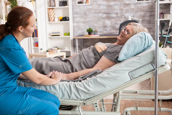 Smiling old woman laying on bed in nursing room