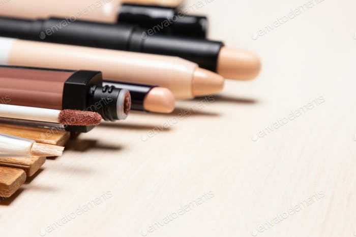 Makeup concealers and foundation in a row on white wooden table