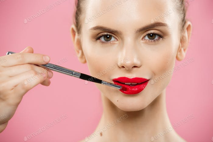 Beauty concept - Happy fashion Caucasian woman with long hair and red lips posing over pink Studio
