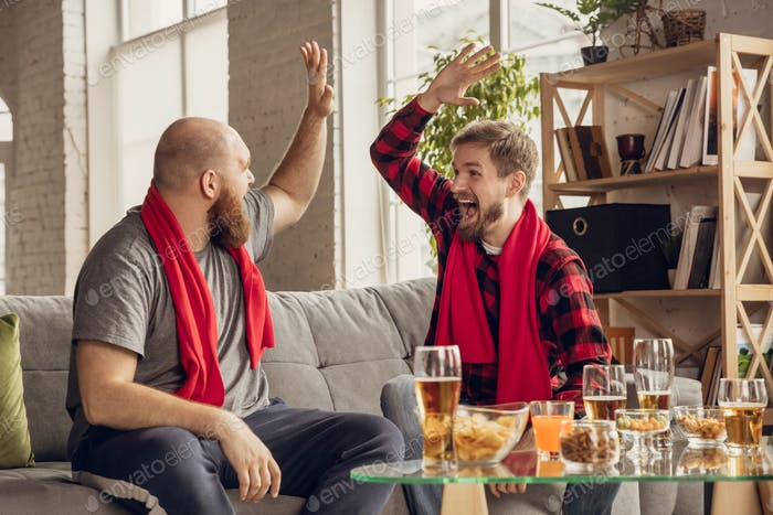 Excited, happy friends watch sport match together on the couch at home