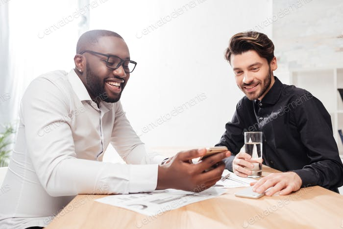 Joyful multinational businessmen sitting at the table happily talking working together in office