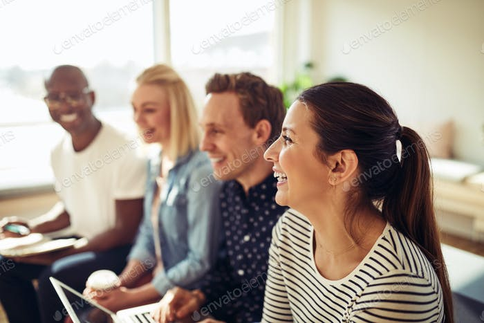Diverse businesspeople laughing together during an office presentation