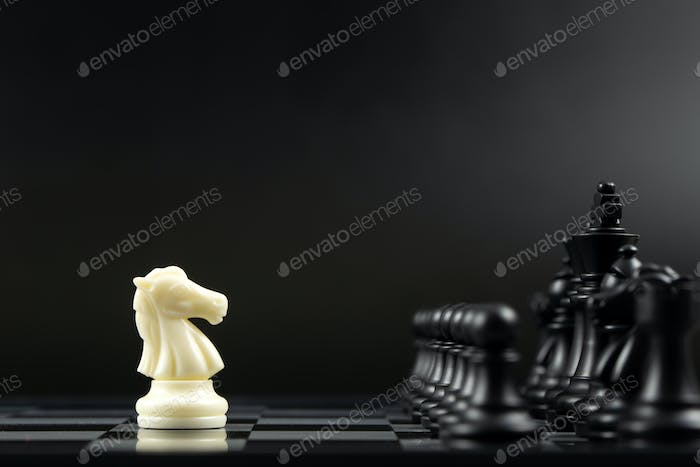 White knight chess piece against all black chess pieces