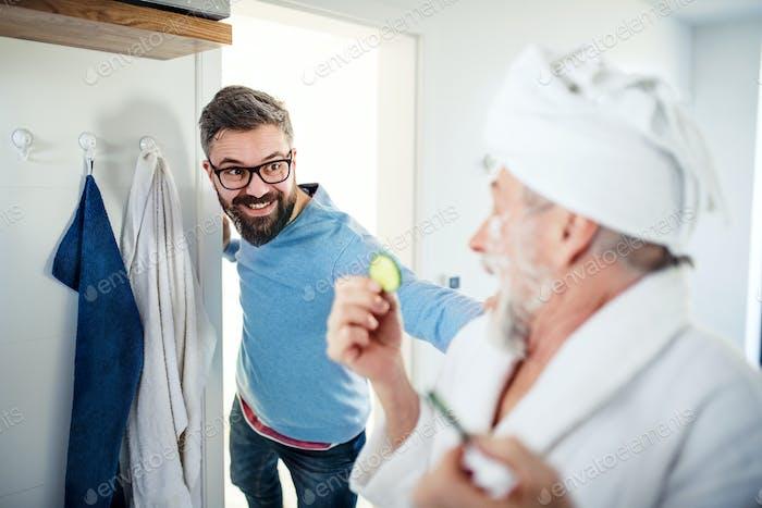 Ein erwachsener Hipster Sohn und Senior Vater im Bad drinnen zu Hause, Spaß haben