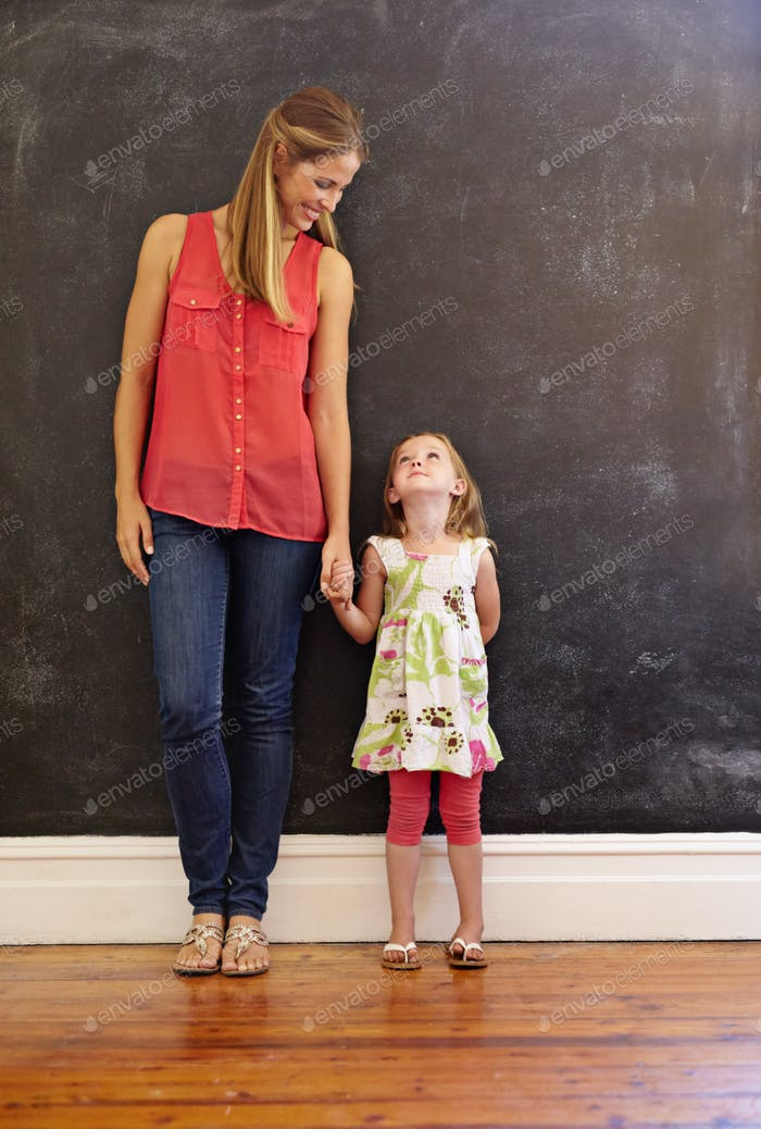 Mother and daughter standing together at home
