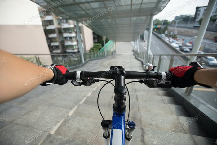 Riding bike going down the stairs of overpass