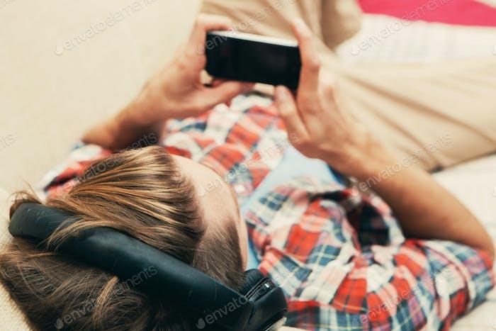 Junger Mann in Kopfhörern mit Handy entspannendes Zuhause
