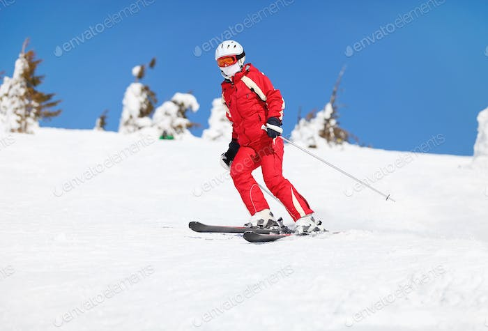 Young female skier on a mountain slope