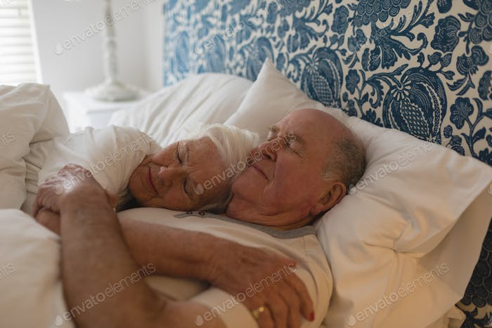 Senior couple embracing together while sleeping in bedroom