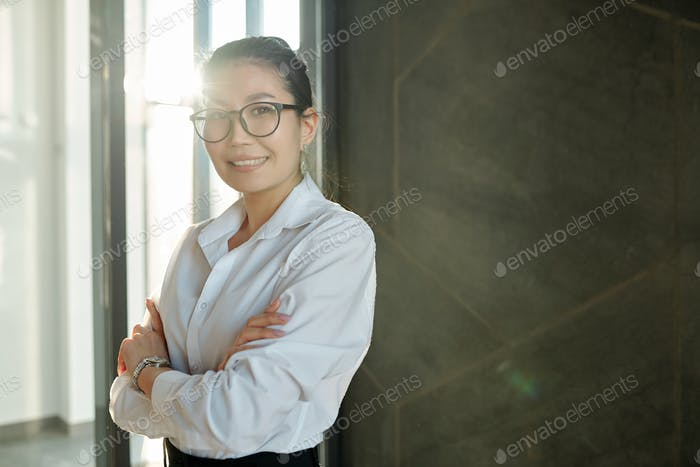 Pretty young smiling businesswoman of Asian ethnicity crossing arms by chest