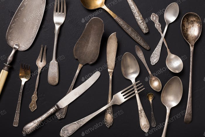 Silver vintage cutlery on black backgound, top view