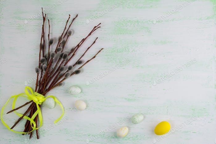 Frohe Ostern Begrüßung mit Eiern und Weidenzweig.