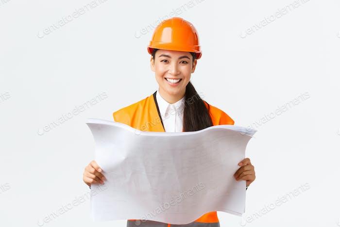 Lächelnd ziemlich asiatische weibliche Architektin, Industrie-Frau in Sicherheitshelm und reflektierende Jacke