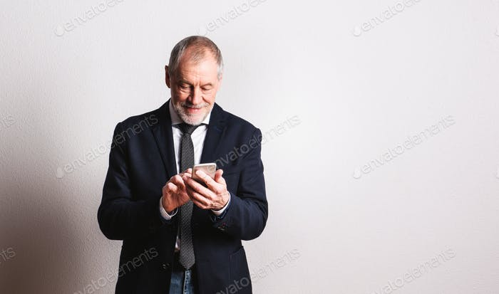 Portrait of a senior man with smartphone in a studio, text messaging