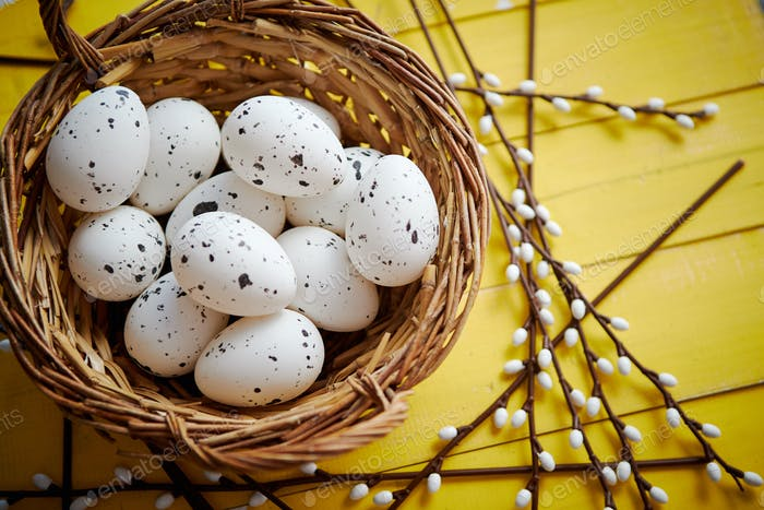Whole chicken eggs in brown wicker basket. The concept of Easter Holidays