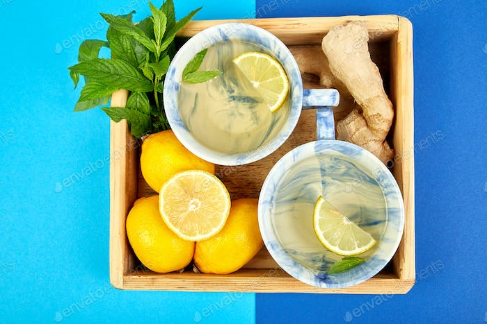Healthy tea two cups with lemon, ginger, mint