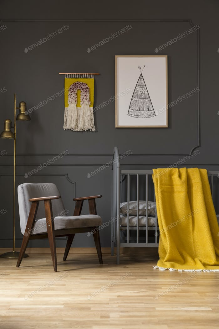 Grey armchair next to bed with yellow blanket in baby's bedroom