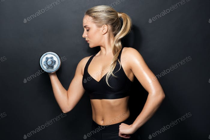 young sporty woman exercising with dumbbell