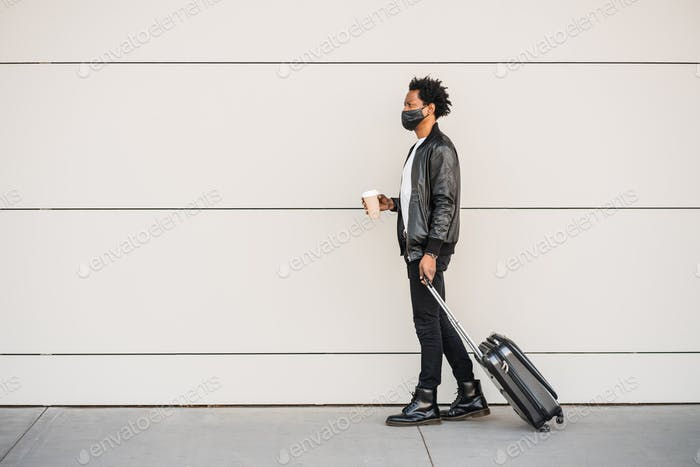Tourist man carrying suitcase while walking outdoors.