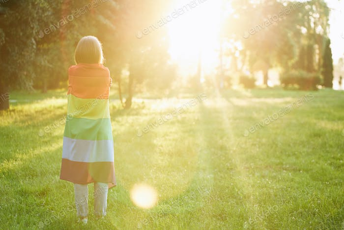Unrecognizable woman holding rainbow flag on shoulders