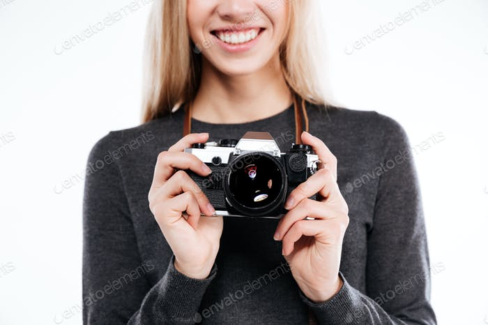 Cropped image of a smiling blonde girl holding retro camera