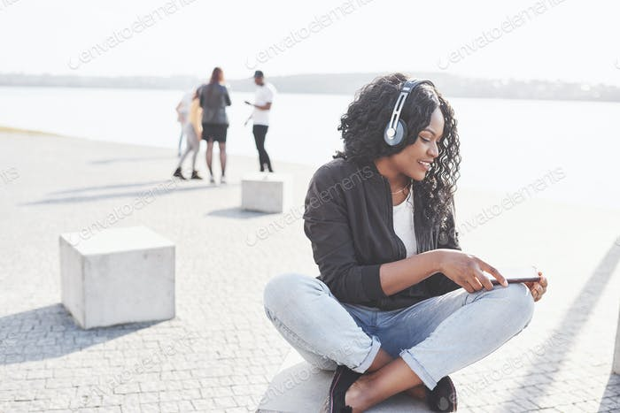young African American girl sitting on the beach or lake and listening to music in her headphones