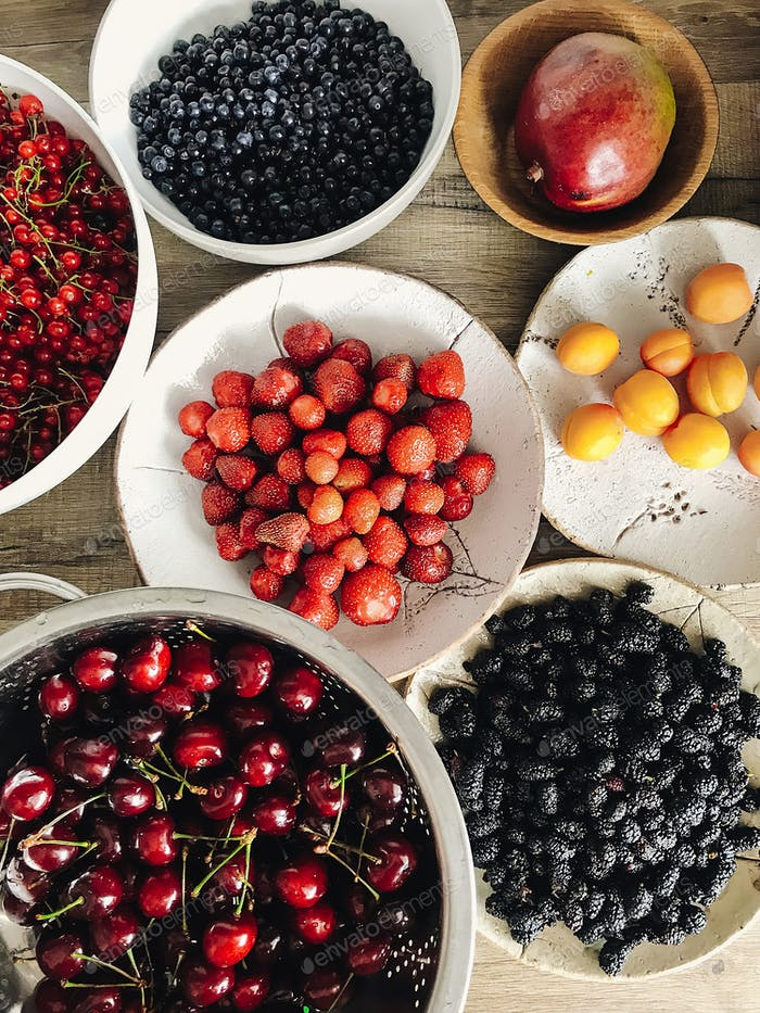 Fresh summer fruits in ceramic bowls on wooden table in the kitchen