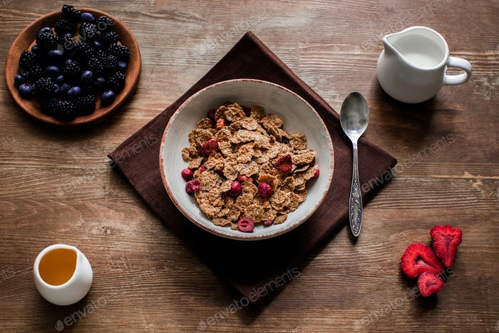 top view of corn flakes and berries on wooden table