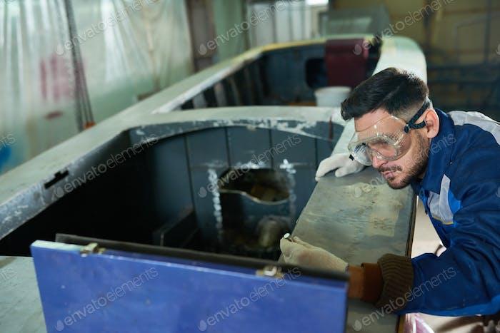 Handsome Man Repairing Boat in Workshop