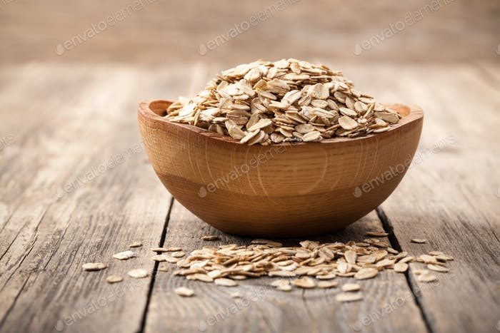 Dry oat flakes in wooden bowl