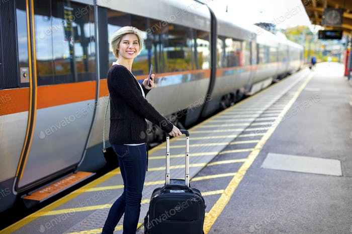 Happy Woman With Mobile Phone And Luggage At Train Station