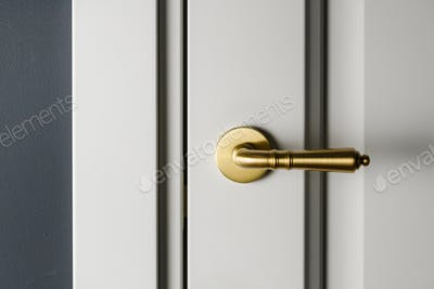 Brushed gold modern design in vintage style door handle on a white door.