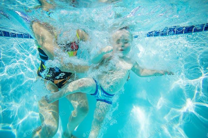 Little boy learning to swim underwater in pool