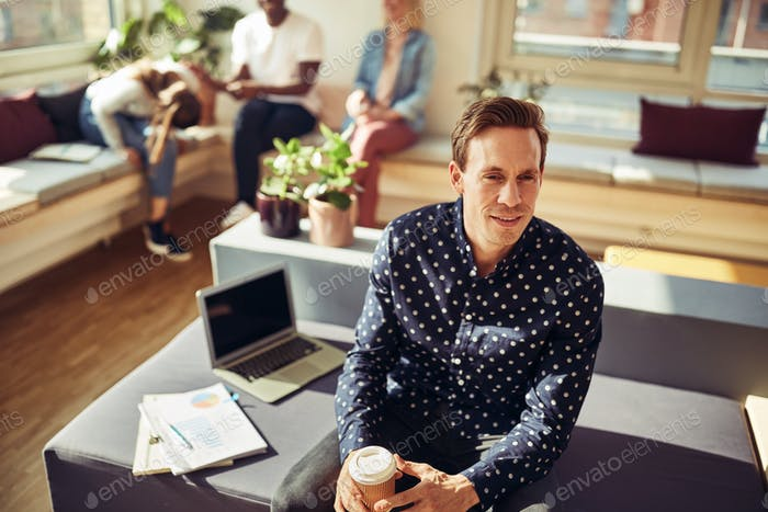 Smiling manager sitting on his desk drinking coffee