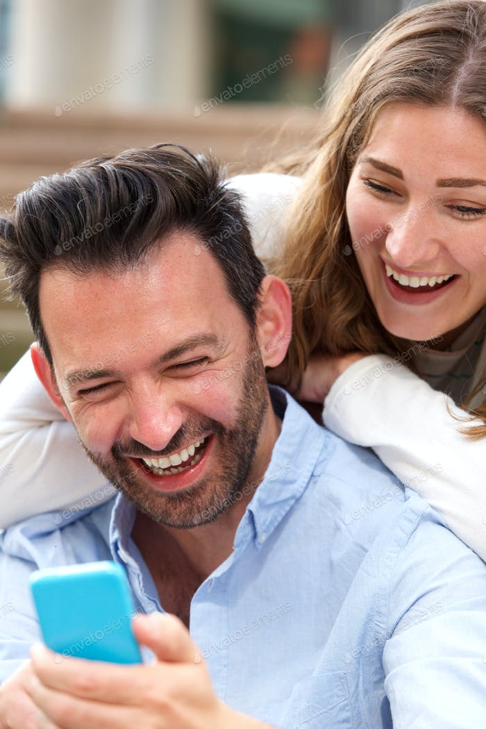 Close up laughing couple sitting together in embrace with mobile phone