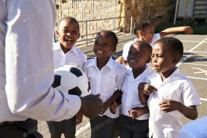 Teacher with ball and kids in elementary school playground